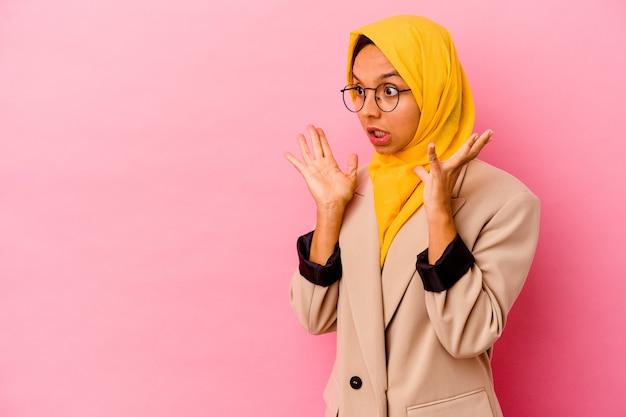 Junge geschäftsmuslimfrau, die auf rosa wand isoliert ist, schreit laut, hält augen offen und hände angespannt.