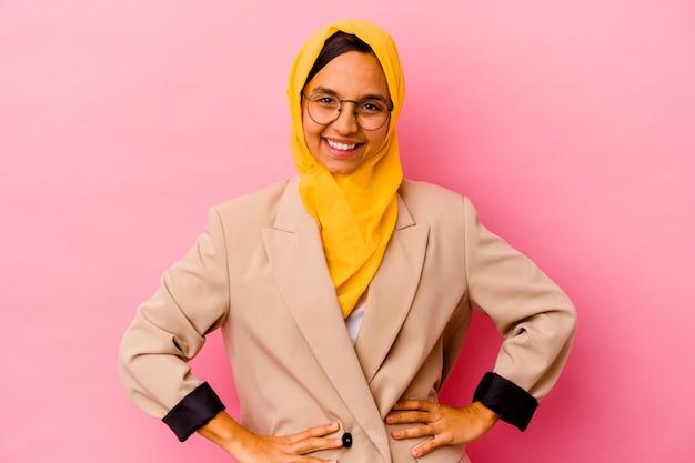 Junge geschäftsmuslimfrau lokalisiert auf rosa wand zuversichtlich hände auf hüften haltend