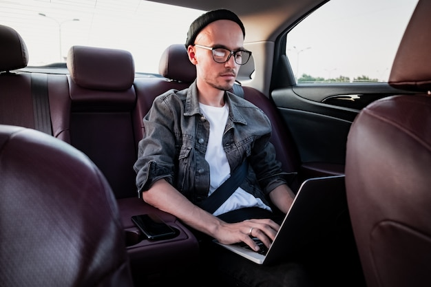 Junge geschäftsperson, die laptop auf einem rücksitz eines autos verwendet.