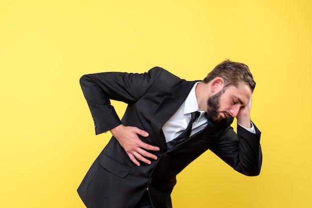 Junge geschäftsperson, die unter bauchschmerzen und kopfschmerzen leidet
