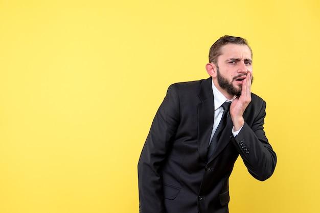 Junge geschäftsperson, die unter zahnschmerzen auf gelb leidet