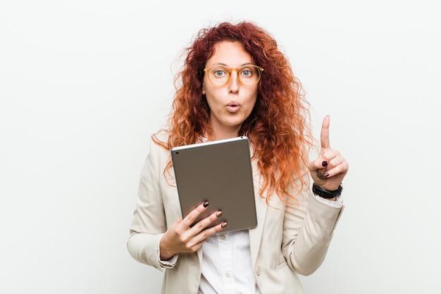 Junge geschäftsrothaarigefrau, die eine tablette hat irgendeine großartige idee hält