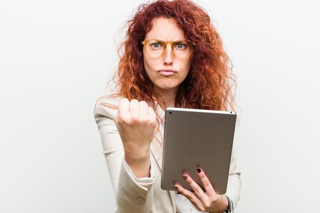 Junge geschäftsrotschopffrau, die eine tablette hält, die faust zeigt