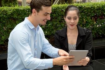 Junge Geschäftsleute sind daran interessiert, Tablet zu spielen.