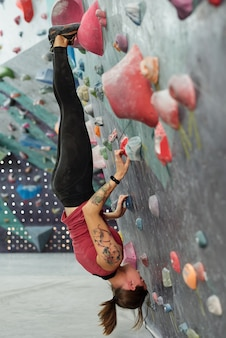Junge geschickte sportlerin, die kopfüber mit ihren füßen und händen hängt, die durch künstliche felsen auf kletterwand halten