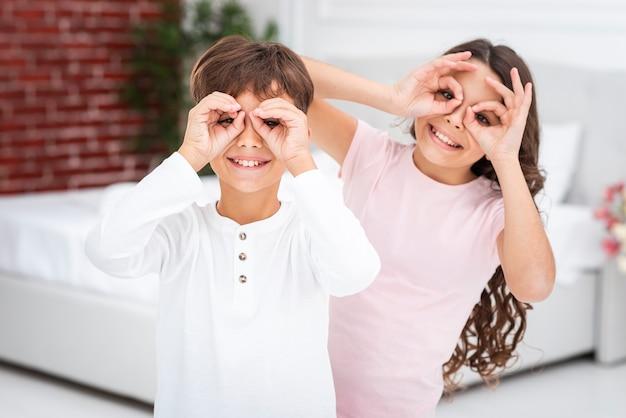 Junge geschwister, die binokular mit den händen machen
