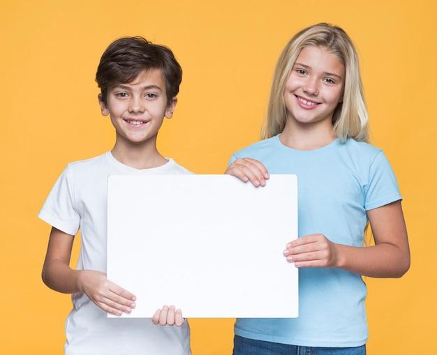 Junge geschwister, die blatt des leeren papiers halten