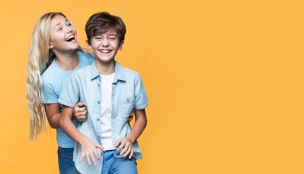 Junge geschwister, die mit kopieraum umarmen