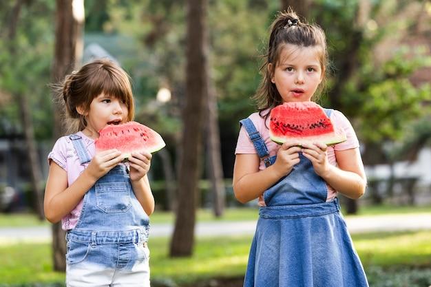 Junge geschwister, die wassermelone draußen essen
