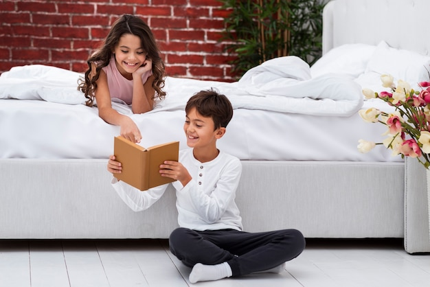 Junge geschwister, die zusammen geschichten lesen