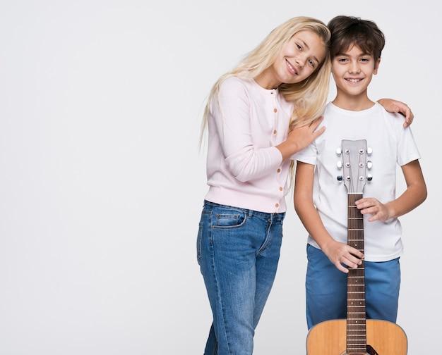Junge geschwister mit gitarre