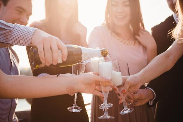 Junge gesellschaft gießt champagner in die weingläser. junge leute trinken champagner bei sonnenuntergang. prickelnder champagner in glasbechern. spritzer champagner