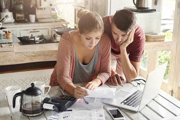Junge gestresste familie, die stromrechnungen online mit laptop zahlt. besorgte frau hält dokument, berechnung der haushaltskosten zusammen mit ihrem ehemann