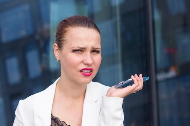 Junge gestresste frau bekam schlechte negative nachrichten auf dem handy und wurde sehr wütend und nervös. stressige missfallene erschrockene frau, die auf dem smartphone im freien spricht. mädchen mit angewidertem gesicht