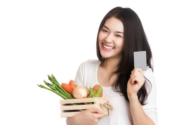 Junge gesunde asiatische frau mit frischem bio-gemüse im korb, hand, die kreditkarte hält.