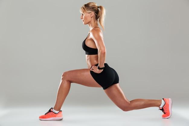 Junge gesunde fitnessfrau, die ausfallschrittübungen tut