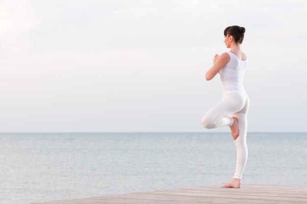 Junge gesunde frau, die auf einem bein steht, während im freien auf see meditiert und betet