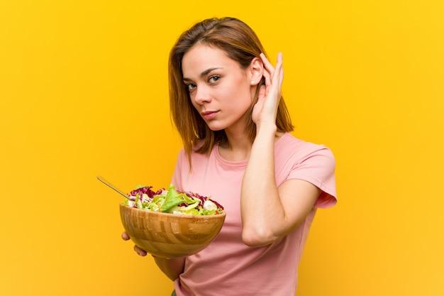 Junge gesunde frau, die einen salat versucht, einen klatsch zu hören hält