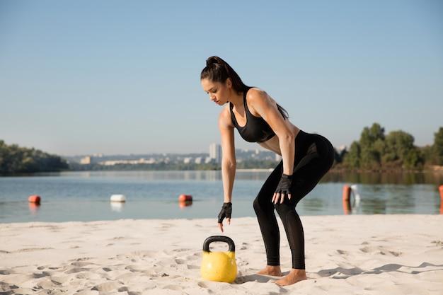 Junge gesunde frau, die kniebeugen mit gewichten am strand tut.