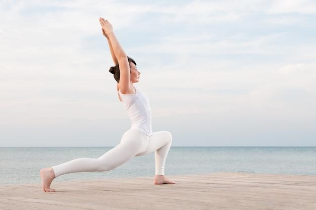 Junge gesunde frau, die mit yoga-haltung am meer meditiert und ausübt