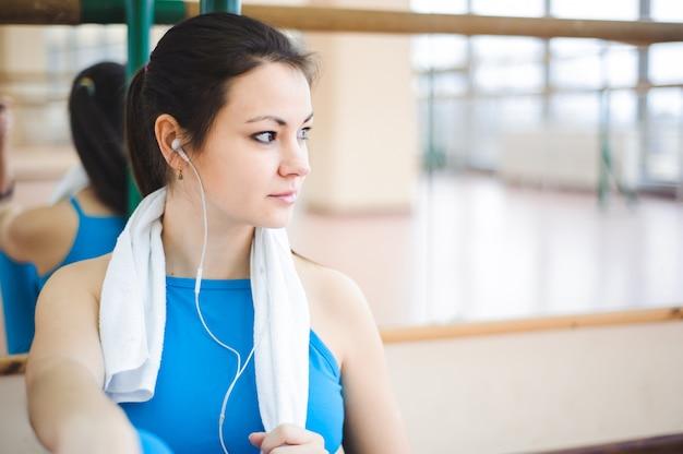 Junge gesunde frau, die musik auf kopfhörern in der eignung hört.
