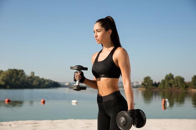 Junge gesunde frau, die oberkörper mit gewichten am strand trainiert.