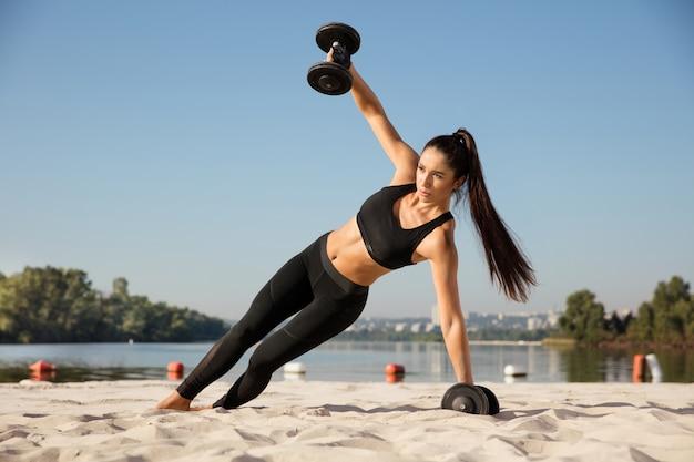 Junge gesunde frau, die oberkörper mit gewichten am strand trainiert