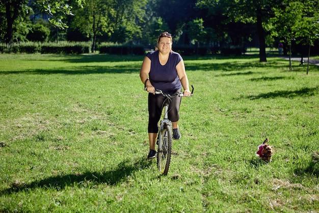 Junge gesunde frau fährt fahrrad im park mit kleinem hund, der in der nähe läuft