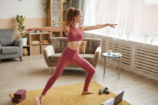 Junge gesunde frau in der sportkleidung, die dehnungsübungen im raum tut, während fitnesslektion auf laptop beobachtet