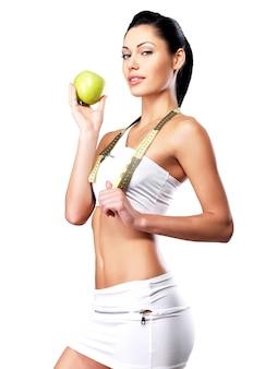 Junge gesunde frau mit apfel nach diät. sportliche frau mit perfekter figur