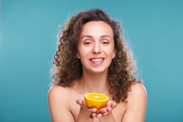 Junge gesunde fröhliche frau mit zahnigem lächeln und luxuriösem braunem gewelltem haar, das die hälfte der frischen orange zeigt und nach vorne schaut