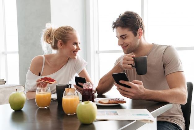 Junge gesunde paare unter verwendung ihrer smartphones beim essen des frühstücks