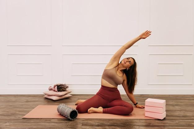 Junge gesunde schöne frau in der sportlichen spitze und in den leggings, die yoga zu hause praktizieren, streckt körper auf yogamatte, die entspannt mit geschlossenen augen lächelt, gesundes lebensstilkonzept