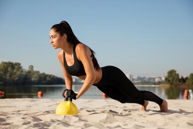 Junge gesunde sportlerin, die training am strand macht