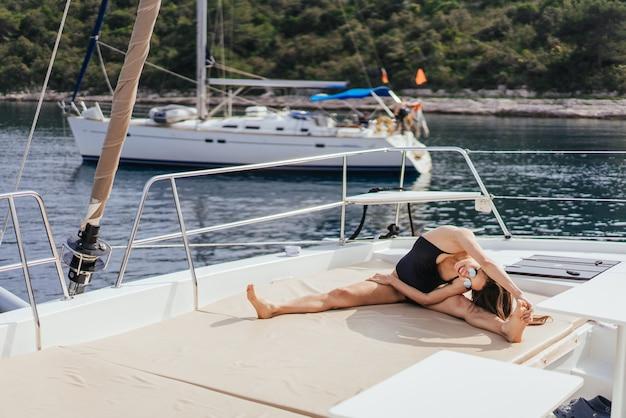 Junge gesunde und ruhige frau, die yoga auf segeljachtboot im meer tut