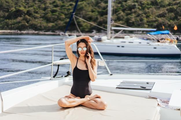 Junge gesunde und ruhige frau, die yoga auf segelyachtboot im meer auf der insel tut