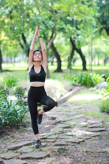 Junge gesunde und sportliche frau tun das yogaausdehnen im freien