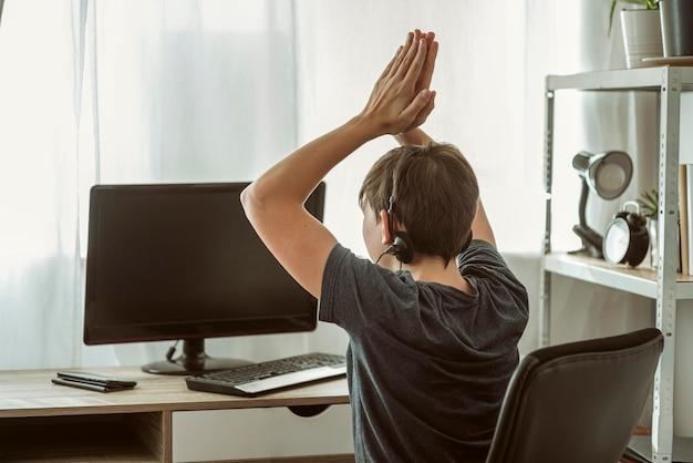 Junge gewinnt ein online-spiel mit seinen freunden