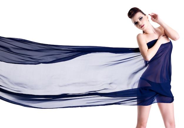 Junge glamour-sinnlichkeitsfrau, die sich auf chiffon anzieht - horizontal