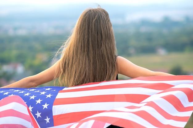 Junge glückliche amerikanische frau mit dem langen haar, das das winken auf wind usa-nationalflagge auf ihren schultern hält, die im freien sich entspannen, die warmen sommertag genießen.