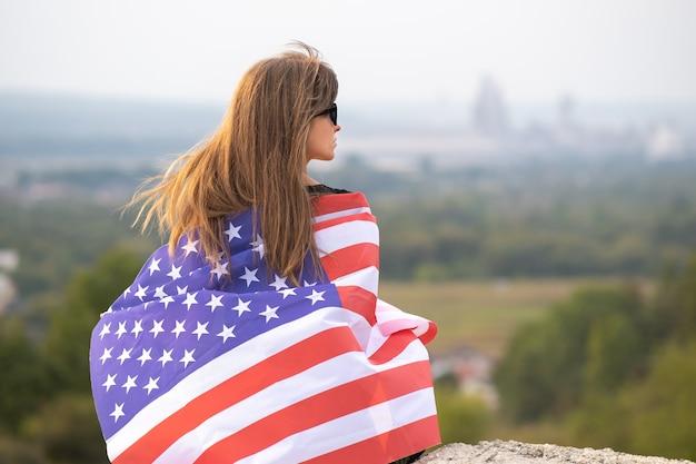 Junge glückliche amerikanische frau mit langen haaren, die auf wind usa-nationalflagge auf ihren sholdern winkt, die sich im freien entspannen und einen warmen sommertag genießen.