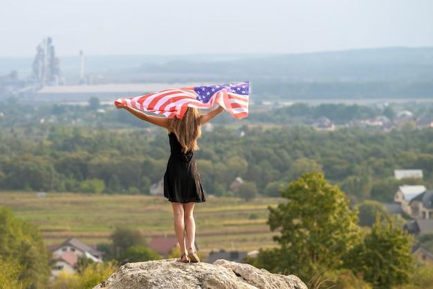 Junge glückliche amerikanische frau mit langen haaren, die auf wind usa-nationalflagge in ihren händen winken, die sich im freien entspannen und warmen sommertag genießen.