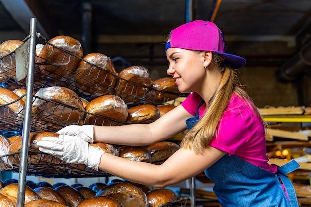 Junge glückliche arbeiterin in sterilen tüchern mit frisch gebackenen muffins auf weißblech in der lebensmittelfabrik.