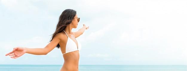 Junge glückliche asiatin im weißen badeanzug am strand an den sommerferien