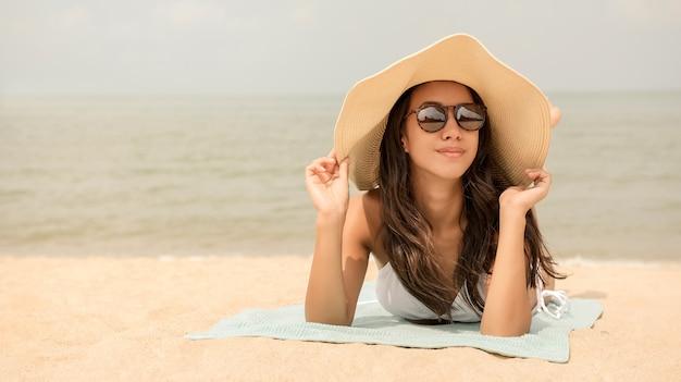 Junge glückliche asiatin mit dem sunhat, der am strand im sommer liegt