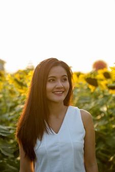 Junge glückliche asiatische frau, die lächelt und denkt, während sie seite betrachtet