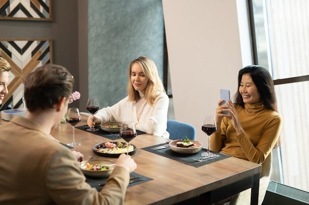 Junge glückliche asiatische frau mit smartphone, die beim abendessen ein foto von jungs macht, während sie am servierten tisch im restaurant unter ihren freunden sitzt?