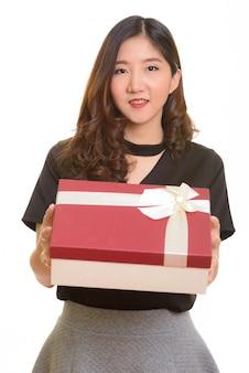 Junge glückliche asiatische geschäftsfrau, die geschenkbox bereit für valentinstag gibt