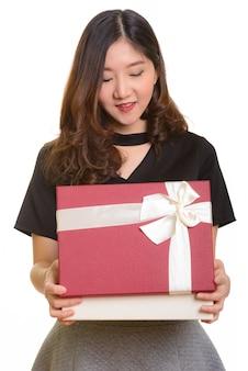 Junge glückliche asiatische geschäftsfrau, die geschenkbox öffnet, bereit für valentinstag