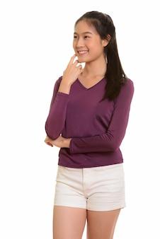 Junge glückliche asiatische teenager-mädchen lächelnd und denkend